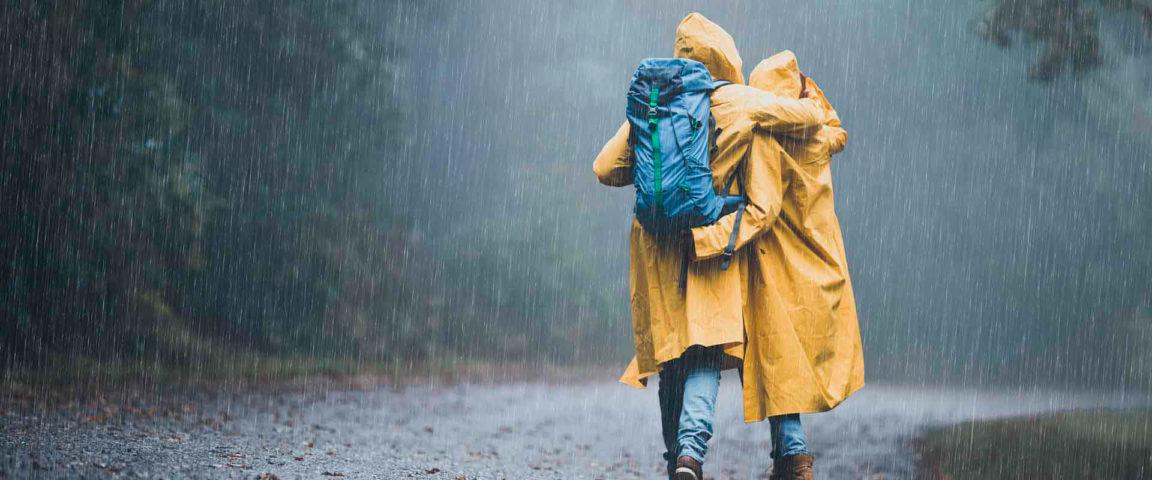Pariskunta kävelee satessaa keltaisissa sadetakeissa