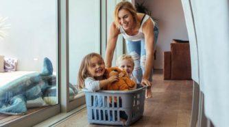 Äiti työntää lapsia pyykkikorissa