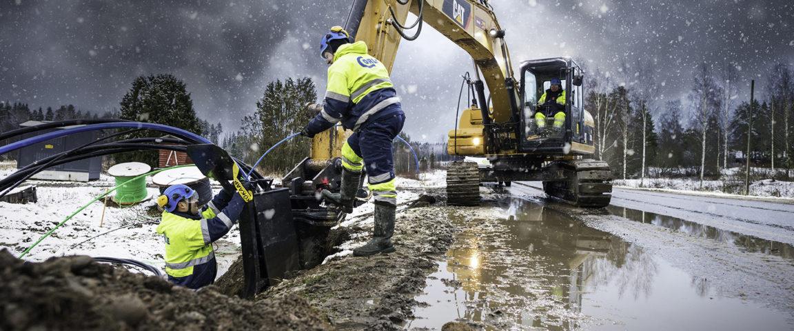 Käynnissä sähköverkon maakaapelointi, kaivuri ja työmiehiä