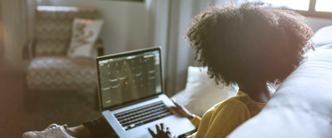 Nainen istu sohvala kannettava tietokone sylissä