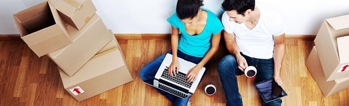 Nuori nainen ja mies istuvat lattialla muuttolaatikoiden vieress sylissään kannettava tietokone