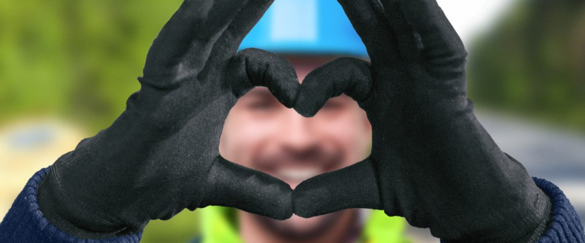 Sähköasentaja työvaatteissa ja tekee käsillään sydämen kuvan.