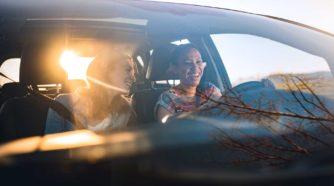 Kaksi iloista nuorta naista autossa