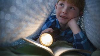 Pieni poika viltistä tehdyssä majassa lukemassa taskulampun valossa