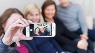 ystäväporukka sohvalla ottamassa selfietä