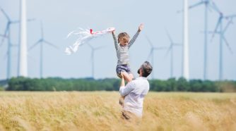 Dad and girl on a field, windmills at the background