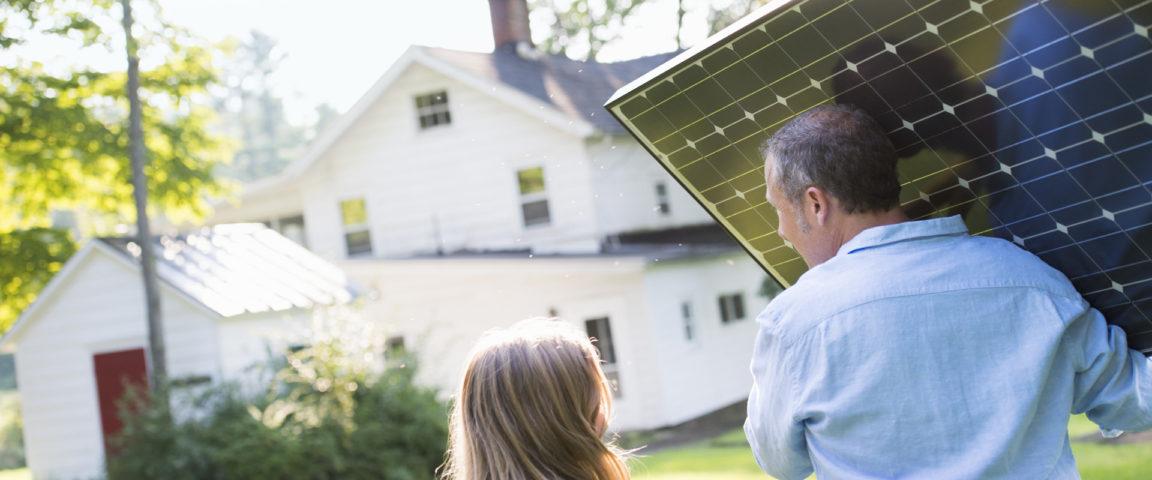 Mies kantaa aurinkopaneelia ja tyttö kävelee vierellä.