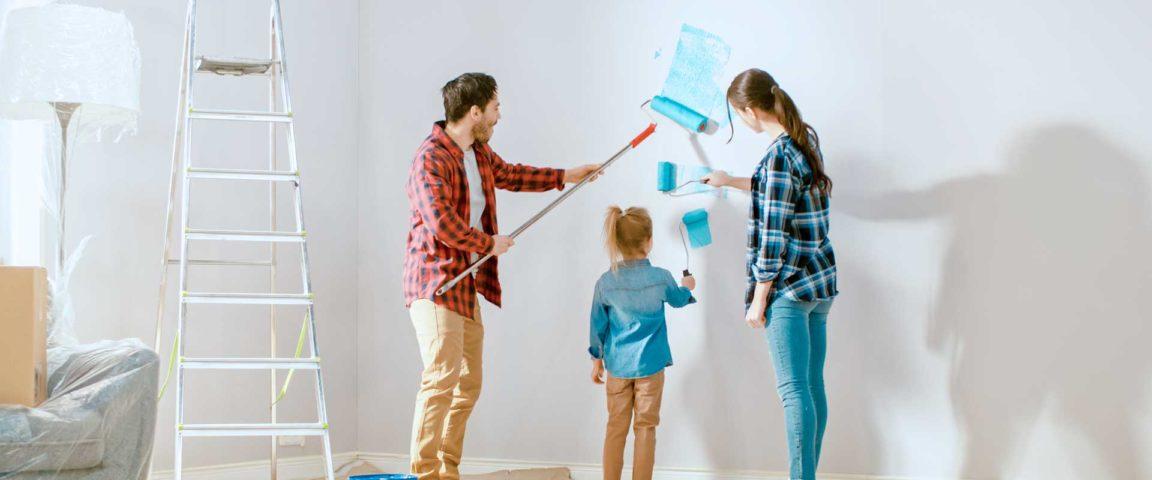 Perhe maalaa uudessa kodissa seinää siniseksi