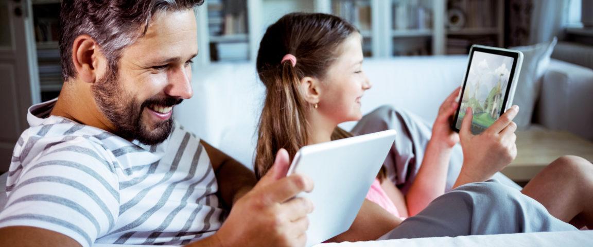 Isä ja tyttö istuvat sohvalla ja molemmilla on tabletit kädessään.