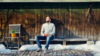 Mies istuu talon seinustalla kahvikuppi kädessä ja ottaa aurinkoa