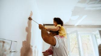 Lapsi miehen hartioilla maalaa kodin sisäseinää