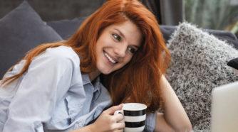 Elenia Kuitu punatukkaine nainen kannettavan äärellä kahvikuppi kädessään