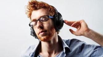 Nuori mies kuuntelee musiikkia kuulokkeista silmät kiinni