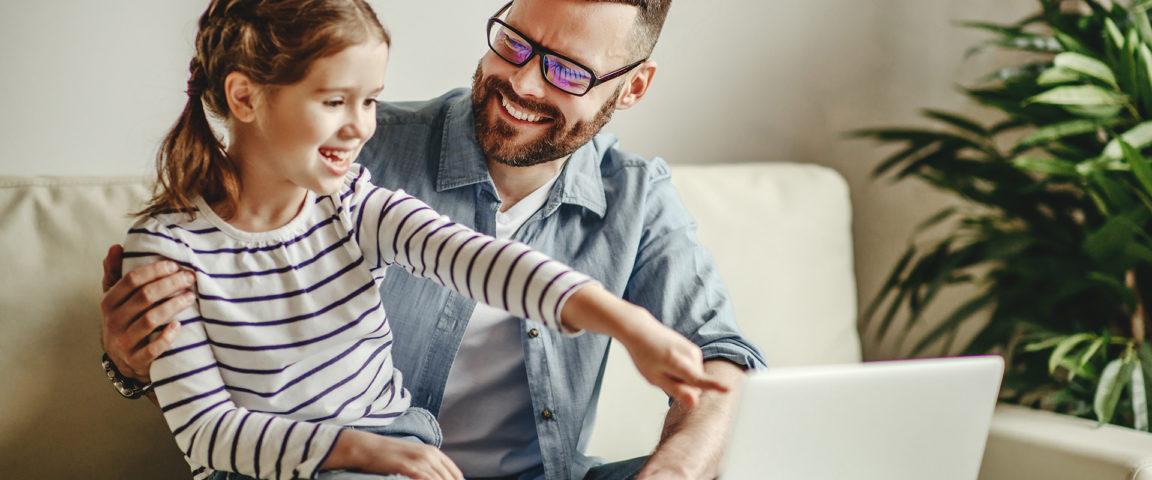 Isä ja tytär katsovat yhdessä kannettavaa tietokonetta