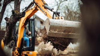 Kaivuri kaivaa kuoppaa pihapiirissä