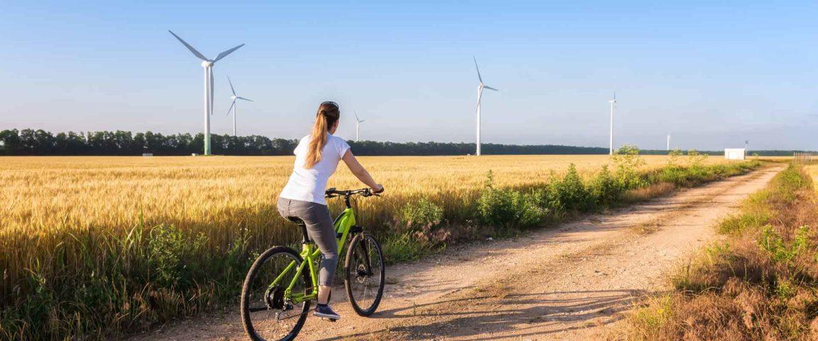 Nainen pyöräilee maaseudulla tuulipuiston ohi