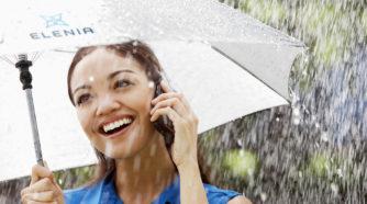 Nainen puhuu kännykkään sateenvarjon alla
