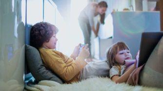 Lapset katselevat tabletteja ja äiti näkyy taustalla