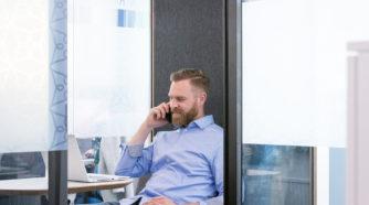 Parrakas mies istuu sohvalla ja puhuu puhelimessa